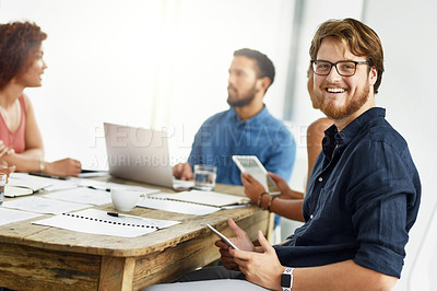 Buy stock photo Portrait of a confident young businessman browsing on his digital tablet while being seated in a meeting inside of the office