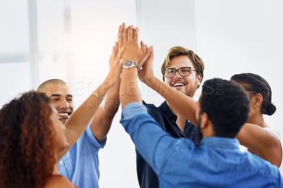 Buy stock photo Cropped shot of a group of confident young work colleagues forming a huddle with their hands at work during the day