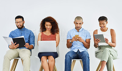 Buy stock photo Shot of a group of confident work colleagues working on their digital devices while being seated and waiting in the office