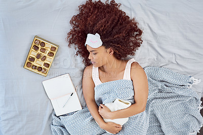 Buy stock photo High angle shot of an attractive young woman suffering from stomach cramps in her bedroom