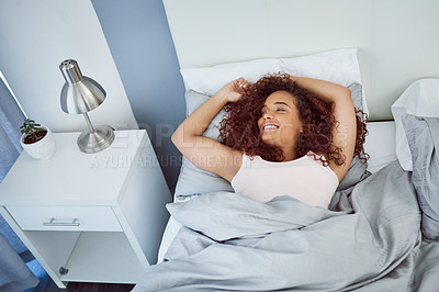 Buy stock photo Shot of an attractive young woman lying in her bed at home