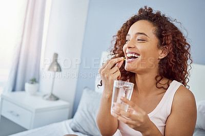 Buy stock photo Shot of an attractive young woman taking her medication in her bedroom at home