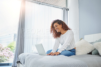 Buy stock photo Shot of a young woman using a laptop in her bedroom at home
