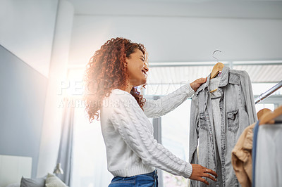 Buy stock photo Shot of a young woman going through clothes from her wardrobe at home
