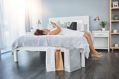 Buy stock photo Shot of a young woman using a cellphone while relaxing on her bed with shopping bags around her