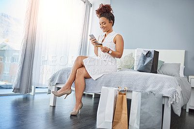 Buy stock photo Shot of a young woman using a cellphone and credit card while relaxing in her bedroom with shopping bags around her