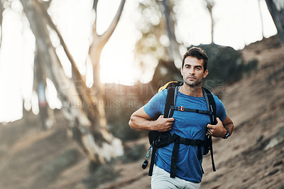 Buy stock photo Cropped shot of a cheerful young man wearing a backpack and ready to hike up a mountain