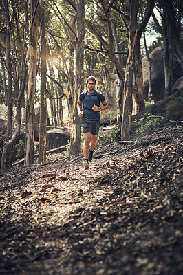 Buy stock photo Full length shot of a handsome young man running during his hike in the mountains