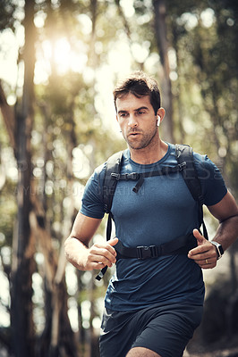 Buy stock photo Cropped shot of a handsome young man running during his hike in the mountains