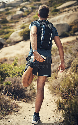 Buy stock photo Rearview shot of an unrecognizable young man stretching before heading off on his hike in the mountains