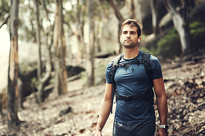 Buy stock photo Cropped shot of a handsome young man out for a hike in the mountains