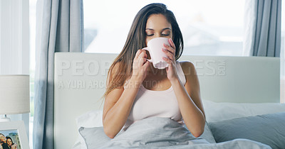 Buy stock photo Cropped shot of a tired young woman waking up and having coffee in bed in the morning hours