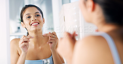 Buy stock photo Cropped shot of a cheerful young woman looking at her reflexion in the mirror and flossing her teeth in the morning
