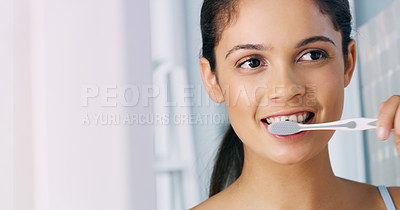 Buy stock photo Cropped shot of a cheerful young woman looking at her reflexion in the mirror while brushing her teeth in the morning