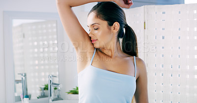 Buy stock photo Cropped shot of a confused looking young woman smelling her armpits in the morning