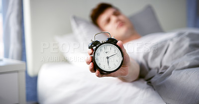Buy stock photo Cropped shot of a young man holding an alarm clock while sleeping in his bed at home
