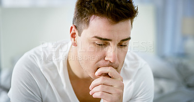 Buy stock photo Cropped shot of a handsome young man looking thoughtful while sitting on his bed