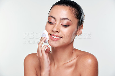 Buy stock photo Shot of a beautiful young woman wiping her face with a cotton pad against a studio background