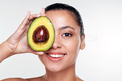 Buy stock photo Shot of a beautiful young woman covering her eye with an avocado against a studio background