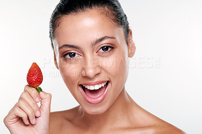 Buy stock photo Shot of a beautiful young woman holding a strawberry against a studio background