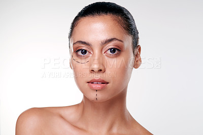 Buy stock photo Shot of a beautiful young woman with cosmetic surgery markings on her face against a studio background