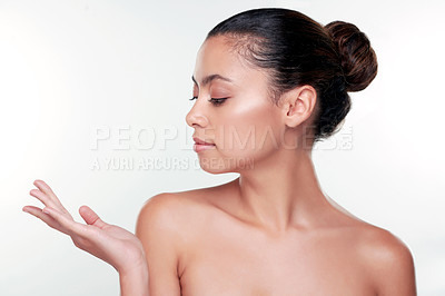 Buy stock photo Shot of a beautiful young woman gesturing towards copy space against a studio background