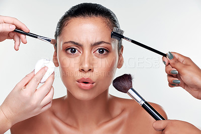 Buy stock photo Shot of hands applying makeup with brushes to a beautiful young woman against a studio background