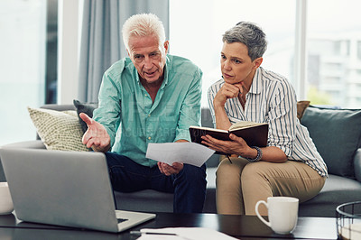 Buy stock photo Shot of a senior couple using a laptop and going through paperwork together while relaxing in their lounge at home