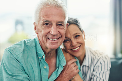 Buy stock photo Portrait of an affectionate senior couple relaxing on their sofa at home