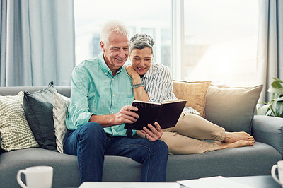 Buy stock photo Shot of an affectionate senior couple reading a book together while relaxing on their sofa at home