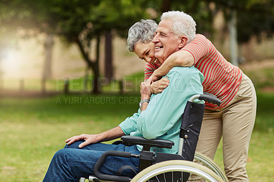 Buy stock photo Shot of a cheerful senior woman relaxing with her wheelchair bound husband at the park