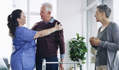 Buy stock photo Shot of a senior man using a walker with his wife and nurse at a retirement home