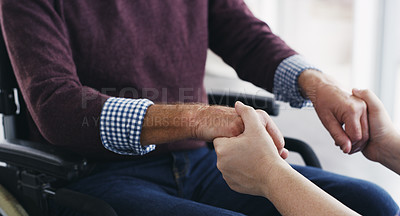 Buy stock photo Cropped shot of a nurse holding hands with a senior man in a wheelchair