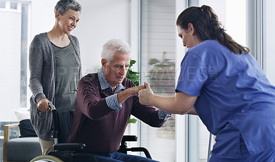 Buy stock photo Shot of a senior man in a wheelchair standing up with the help of a nurse