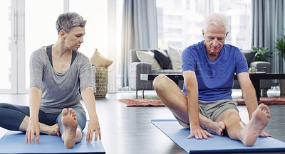 Buy stock photo Shot of a senior couple doing yoga together at home