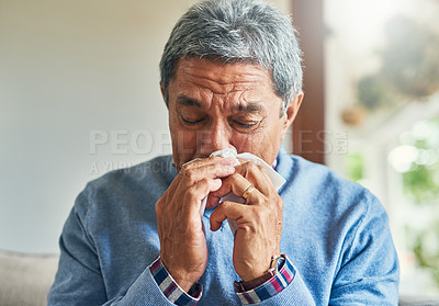 Buy stock photo Shot of a sickly senior man blowing his nose with a tissue at home