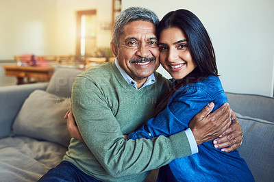 Buy stock photo Portrait of a cheerful senior man posing with his daughter while relaxing on a couch at home
