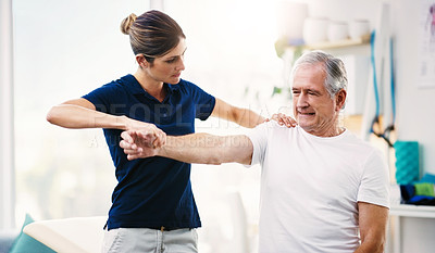 Buy stock photo Shot of an attractive young female physiotherapist working with a senior male patient
