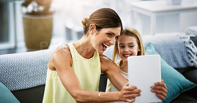 Buy stock photo Shot of a beautiful young mother and her daughter using a digital tablet together in the living room at home