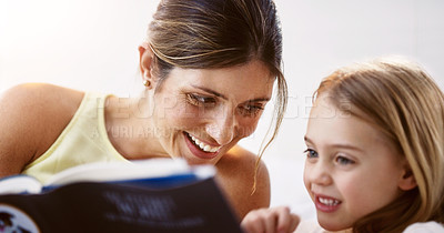 Buy stock photo Shot of a beautiful young mother reading a book with her daughter at home