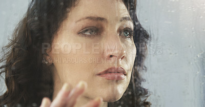 Buy stock photo Closeup shot of a sad young woman standing by a window while it's raining outside