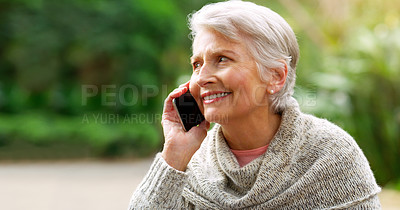 Buy stock photo Cropped shot of a cheerful elderly woman talking on her cellphone outside in a park