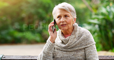 Buy stock photo Cropped shot of a cheerful elderly woman talking on her cellphone while being seated on a bench outside in a park during the day