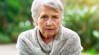 Buy stock photo Portrait of a carefree elderly woman seated on a bench while contemplating outside in a park
