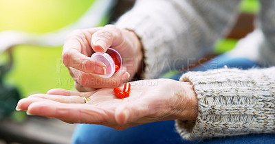 Buy stock photo Cropped shot of an unrecognizable elderly woman about to take medication outside in a park during the day