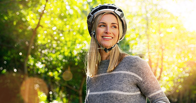 Buy stock photo Cropped shot of a cheerful young woman riding her bicycles outside in a park during the day