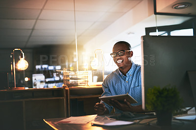 Buy stock photo Cropped shot of a handsome young businessman using a digital tablet during a late night in a modern office