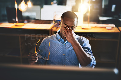 Buy stock photo Cropped shot of a handsome young businessman experiencing stress during late night at work