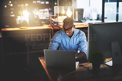 Buy stock photo Cropped shot of a handsome young businessman using a computer during a late night in a modern office