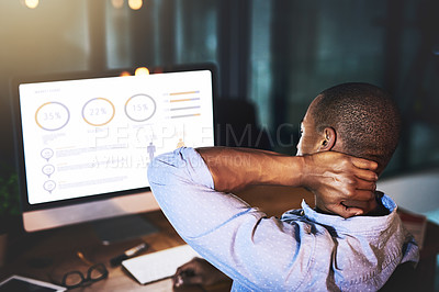 Buy stock photo Rearview shot of an unrecognizable young businessman experiencing tension while using a computer to look at graphs late at work